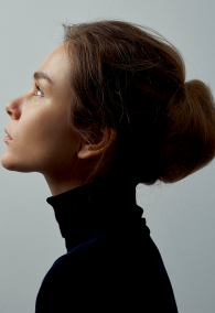 Dramatic portrait of a young beautiful girl with freckles in a black turtleneck on white background in studio