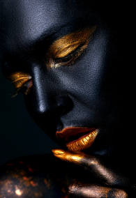 Portrait of a beautiful girl with creative, fantasy make-up. With golden lipstick on a gray background.
