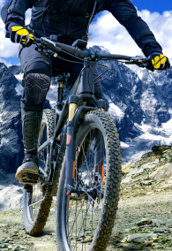 "Mountain bike rider with protectors  rides up a single trail in great height. The background shows the ""Ortler"" mountain massif in the alps."